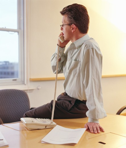 Stock Photo: 1527R-1130401 Man sitting on desk in office using telephone