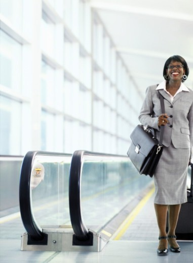 Stock Photo: 1527R-1130608 Woman pulling suitcase on moving walkway in airport, smiling