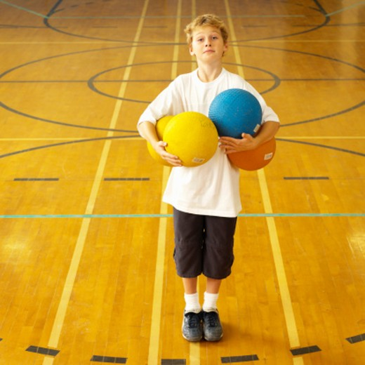 Stock Photo: 1527R-1131212 Boy (9-11) with basketballs in gym, portrait