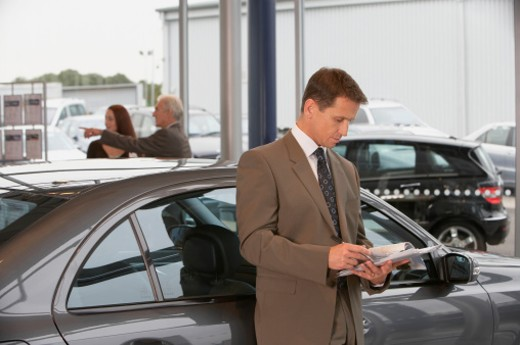 Man leaning against car in showroom, woman and salesman in background : Stock Photo