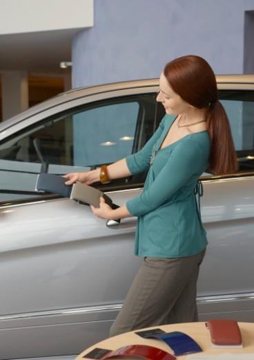 Woman looking at colour samples against car in showroom : Stock Photo