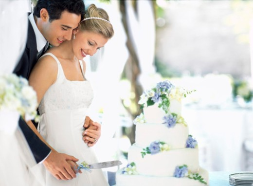 Bride and groom cutting wedding cake, side view : Stock Photo