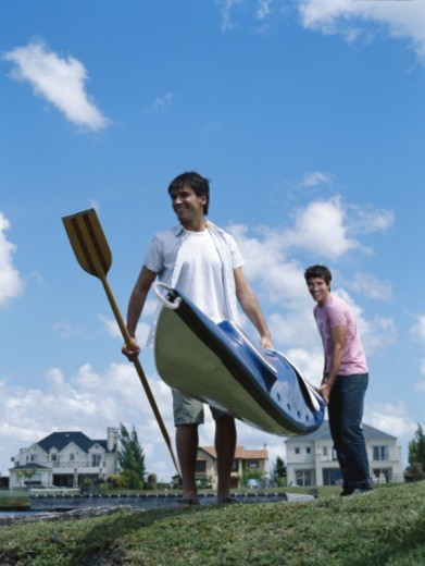 Two young men carrying kayak beside dock, smiling : Stock Photo