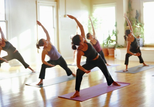 Group of women stretching in yoga class, arms raised : Stock Photo