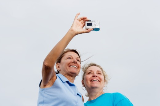 Two mature women taking picture, low angle view, close-up : Stock Photo