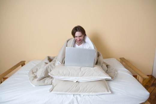 Man covered with blanket using laptop in bed, smiling : Stock Photo