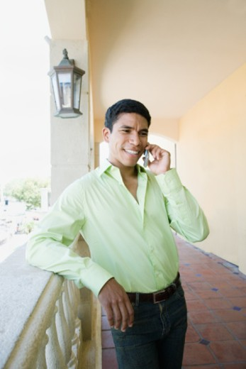 Stock Photo: 1527R-1133667 Man leaning against railing, talking on cell phone