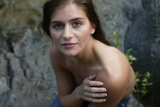 Shirtless young woman sitting on rock, portrait, elevated view : Stock Photo