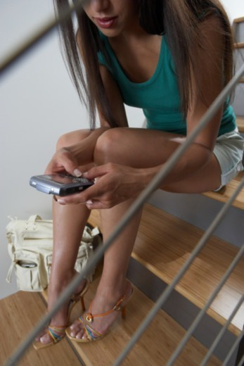 Woman sitting on stairway, using palmtop, low section : Stock Photo