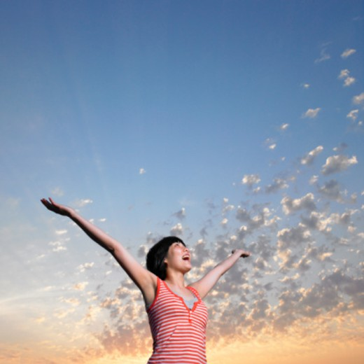 Stock Photo: 1527R-1136359 Young woman with arms outstretched, looking to sky, low angle view