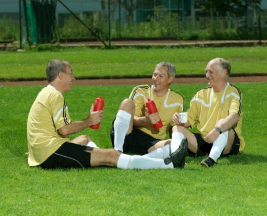 Three mature football players having rest : Stock Photo