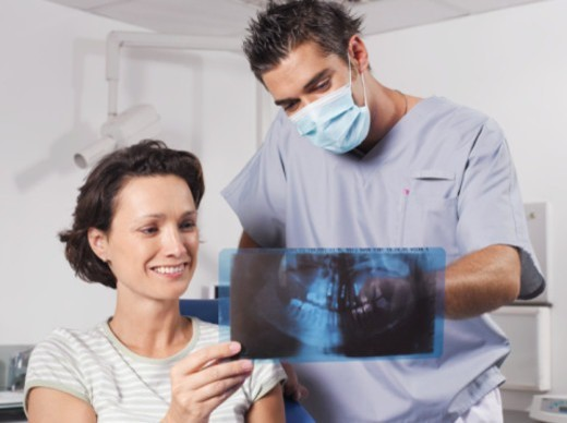 Stock Photo: 1527R-1136659 Woman in dentist's chair, looking at X-Ray smiling