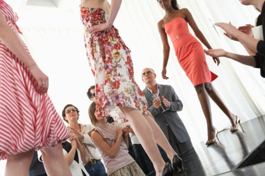Stock Photo: 1527R-1137672 Spectators applauding for models on runway during fashion show