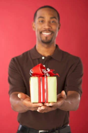 Stock Photo: 1527R-1138016 Young man holding gift, smiling (focus on gift in foreground)