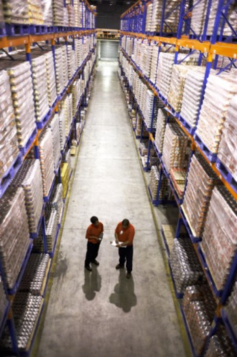 Stock Photo: 1527R-1138972 Two men standing in warehouse aisle checking file, elevated view