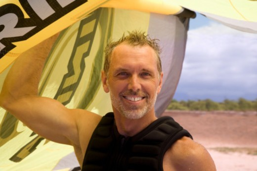 Mature man on beach, holding kite for kite surfing, smiling, portrait : Stock Photo