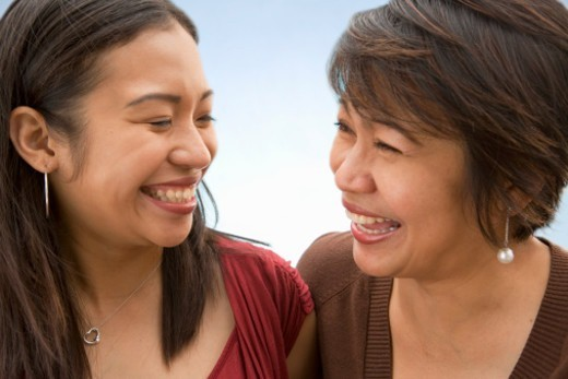 Mother and adult daughter looking at one another, laughing : Stock Photo