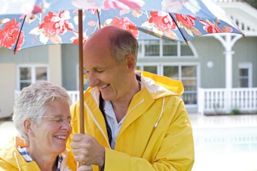 Stock Photo: 1527R-1141243 Senior couple beneath umbrella, smiling