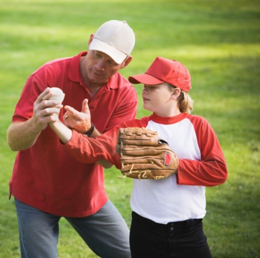 Stock Photo: 1527R-1141670 Coach showing boy (9-11) how to hold baseball