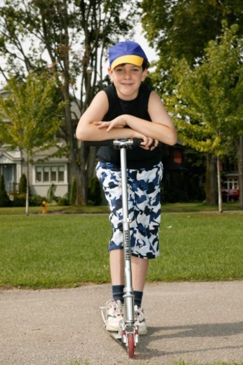 Boy (9-11) standing on push scooter, portrait : Stock Photo