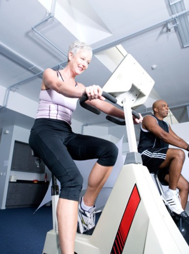 Man and mature woman riding exercise bikes in gym, smiling : Stock Photo