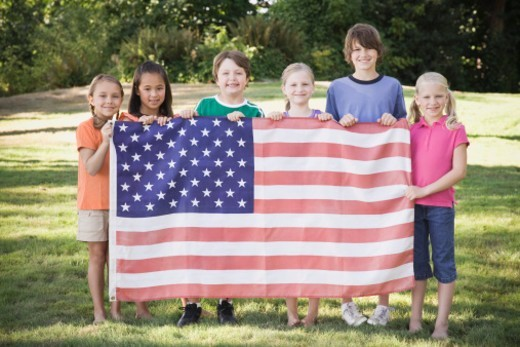 Stock Photo: 1527R-1142146 Six children (7-12) holding American flag outdoors, portrait