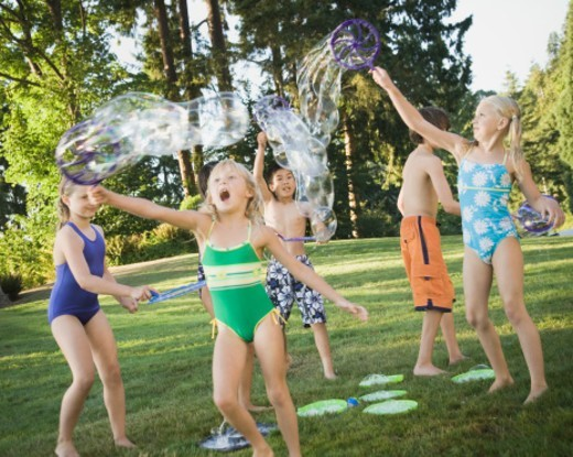 Stock Photo: 1527R-1142158 Group of children (7-12) blowing bubbles outdoors