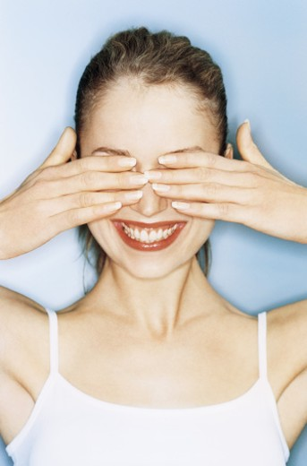 Young woman covering eyes with hands, smiling, close-up : Stock Photo