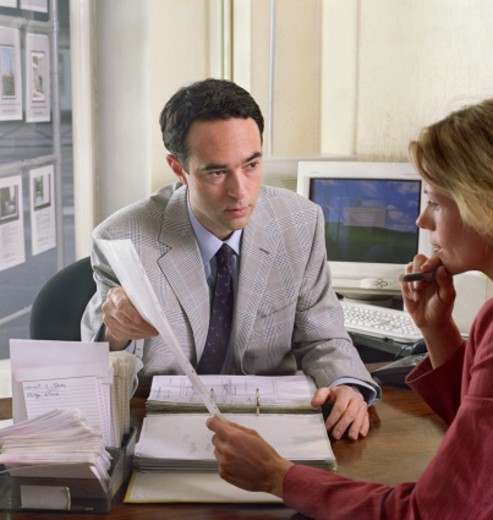 Stock Photo: 1527R-1142500 Businessman showing documents to businesswoman in office