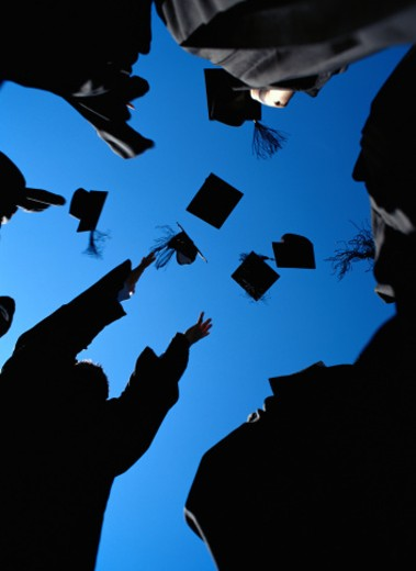 Graduates throwing their mortarboards in the air, low angle view : Stock Photo