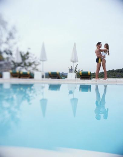 Stock Photo: 1527R-1143292 Couple Hugging Alongside a Swimming Pool