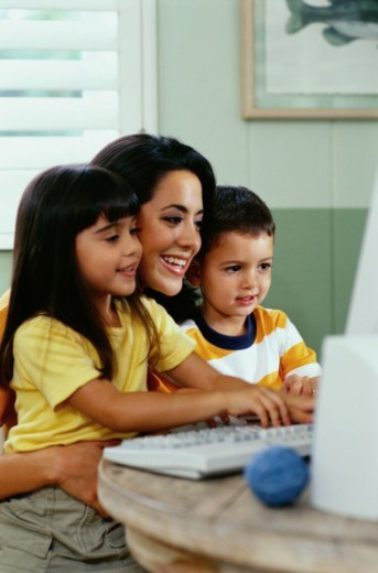 Mother and Her Two Children Using a Computer : Stock Photo