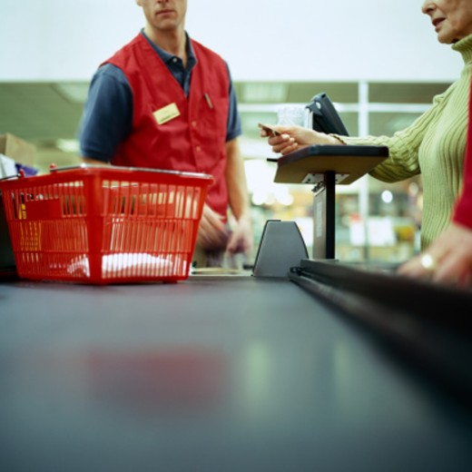 Stock Photo: 1527R-1143737 Woman in supermarket using credit card, mid section