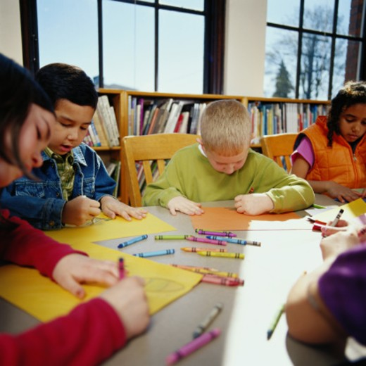 Children (8-10) coloring with crayons at table in classroom : Stock Photo