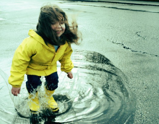 Stock Photo: 1527R-1144575 Girl (3-5) jumping in puddle wearing rain gear