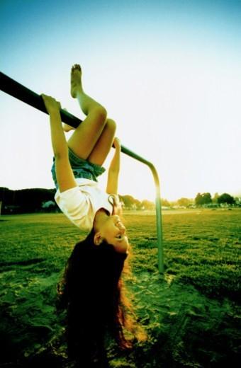 Girl swinging on jungle gym : Stock Photo