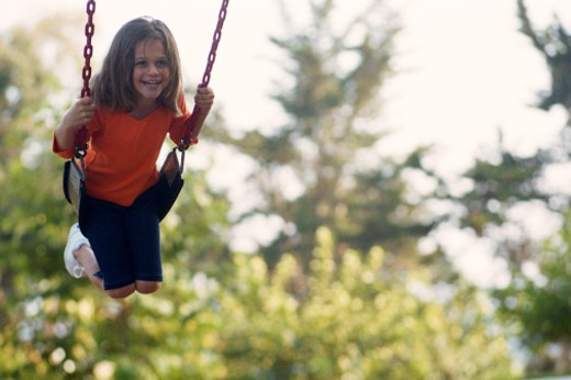 Stock Photo: 1527R-1145449 Girl (7-9) on swinging