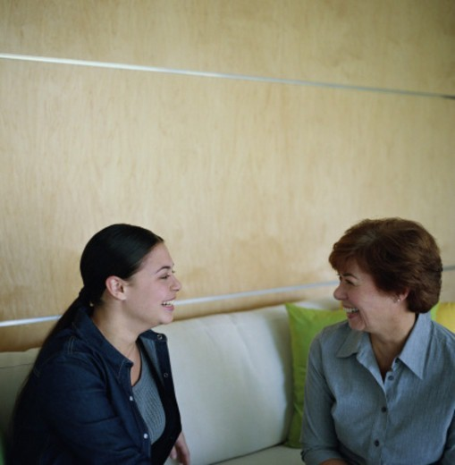 Stock Photo: 1527R-1145733 Mother and adult daughter sitting on sofa, laughing