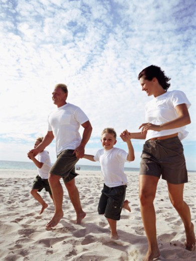 Stock Photo: 1527R-1146219 Parents and sons (4-8) skipping along beach