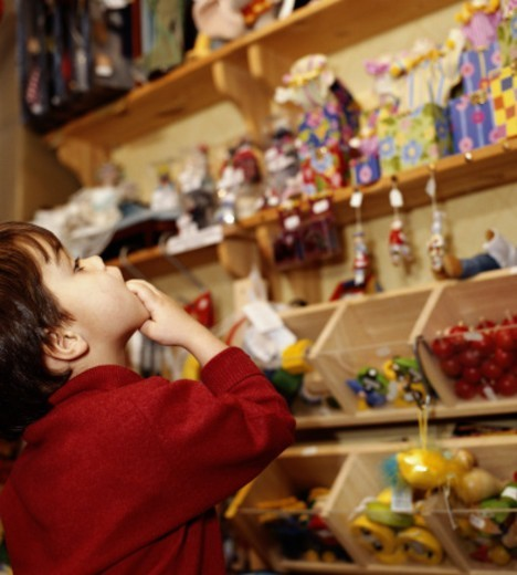 Boy (3-5) looking at toys in shop, side view : Stock Photo
