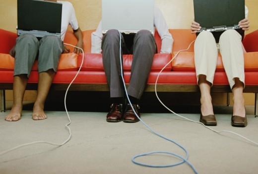 Three executives on sofa using laptops, low section : Stock Photo