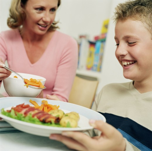 Mother putting vegetables on son's (10-12) plate : Stock Photo