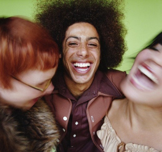 Young man lauging with 2 young women, close-up (selective focus) : Stock Photo