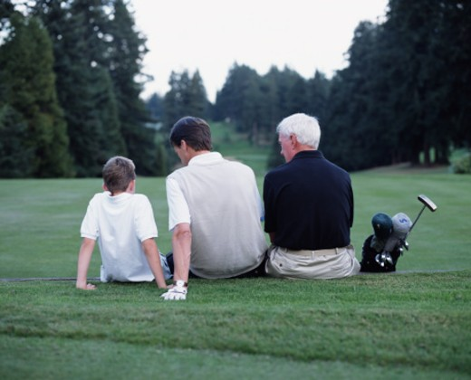 Stock Photo: 1527R-1149236 Grandfather, father and son (8-10) sitting on golf course, rear view