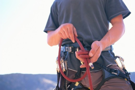 Male rock climber tying knot in climbing rope, middle section : Stock Photo