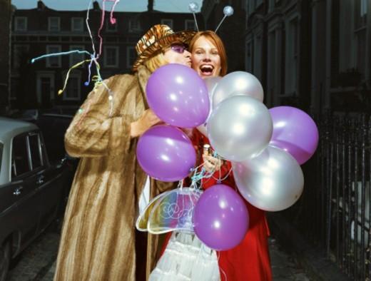 Stock Photo: 1527R-1149481 Man kissing woman holding balloons