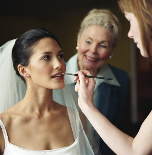 Stock Photo: 1527R-1149521 Bride having lipstick applied while elderly woman looks over shoulder