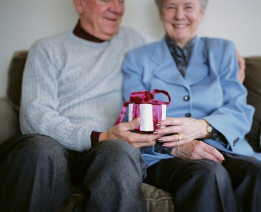 Elderly man and woman exchanging gift (selective focus) : Stock Photo