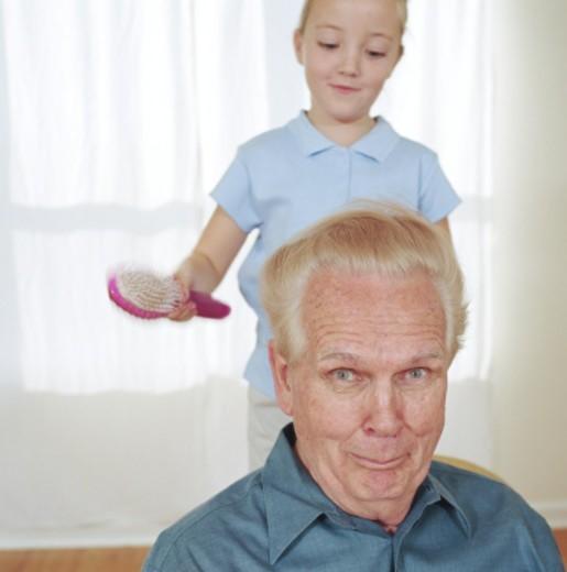Girl (6-8) brushing grandfathers hair : Stock Photo