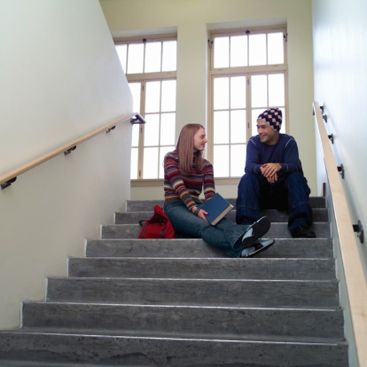 Two teenagers (16-18) talking in high school stairway : Stock Photo